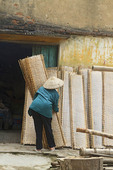Woman in traditional Vietnamese cone hat carries racks of drying rice paper (used in cooking) in Tho Ha village, near Hanoi, Vietnam