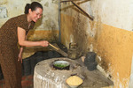 Woman cooks greens for lunch inside the kitchen of her home in Tho Ha village, near Hanoi, Vietnam.