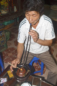 Man smokes using a smoking bowl (Thuoc Lao) in his home in Tho Ha village, near Hanoi, Vietnam.