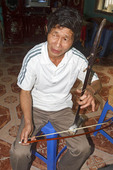 "Man plays a stringed instrument, ""dan nhi"" in his home in Tho Ha village, near Hanoi, Vietnam."
