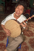 "Man plays a stringed ""moon lute,"" in his home in Tho Ha village, near Hanoi, Vietnam"