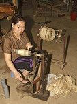 Woman weaves silk into threads at Mao Silk Factory, Hanoi, Vietnam