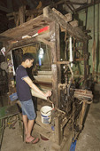 Man works with weaving machine at Mao Silk Factory, Hanoi, Vietnam.