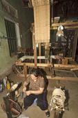 Woman weaves silk into threads at Mao Silk Factory, Hanoi, Vietnam.