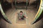 Tourist emerges from Cu Chi Tunnels outside Saigon, Vietnam.