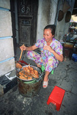 Woman on street in Saigon, Vietnam, cooks food to sell to passersby.