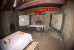 Tourist sits in underground command room from which 1968 Tet offensive was planned. Cu Chi Tunnels near Saigon, Vietnam