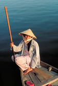 Young Vietnamese woman sits on her boat in Hoi An, central Vietnam.