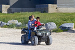 Native family (mother, father and young boy) rides a four wheel ATV around Churchill, Manitoba.