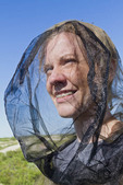 Woman in mosquito head net in the Canadian arctic.