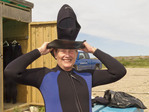 Woman squeezes into wetsuit in preparation for swimming with beluga whales, Churchill, Manitoba, Canada.