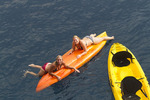 Enjoying some of the water toys aboard American Safari Cruises cruise yacht, Safari Explorer. Here women kayak. Hawaii, USA.