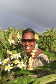 Woman surrounded by plumeria (frangipani) flowers with rainbow in background. Molokai, Hawaii, USA.