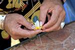 Closeup of local man stringing plumeria (frangipani) flowers to make a lei on Molokai, Hawaii, USA.