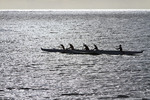 Local youths paddle a traditional outrigger Hawaiian canoe in the waters off Molokai, Hawaii, USA.
