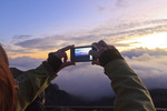 Visitor views scene through LCD screen and photographs sunrise with digital camera over Haleakala Crater, Maui, Hawaii, USA.