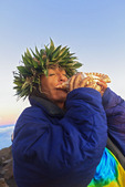 Barbara Bohonu, spiritual/cultural healer greeting sunrise with a chant and blowing a conch shell at Haleakala Crater, Maui, Hawaii, USA.