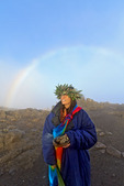 Barbara Bohonu, spiritual/cultural healer greets sunrise and its rainbow with a chant and sage smoke at Haleakala Crater, Maui, Hawaii, USA.