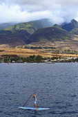 Man enjoys stand up paddleboard in waters of Maui, Hawaii, USA