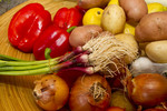 Fresh vegetables including green garlic, onion, peppers and potatoes.