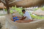 Woman enjoys massage from Maya man while lying in a hammock at Xcaret, an amusement park in Riviera Maya, Yucatan, Mexico.