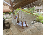 Woman enjoys massage from Maya man while lying in a hammock at Xcaret, an amusement park in Riviera Maya, Yucatan, Mexico.
