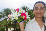 Smiling woman with platter of tropical flowers. Riviera Maya, Yucatan, Mexico.
