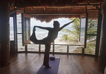 Woman does 'damcer' yoga pose at a beachside resort in Riviera Maya, Yucatan, Mexico.