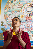 Tibetan Buddhist monk talks about the Wheel of Life which is painted behind him.
