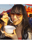 Asian woman eats abalone at Richmond Night Market, Richmond, British Columbia, Canada.