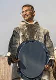 Here, a man wearing seal skin, holds a drum used for dancing in the arctic community of Grise Fjord.