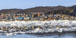 Colorful buildings of Ilulissat reflected in the town's ice choked harbor