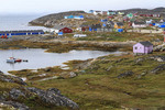 Colorfully painted houses of Itilleq, Greenland, climb low hills around the town harbor.