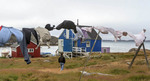 Laundry hangs to dry on a line outside the colorfully painted houses of Itilleq, Greenland.