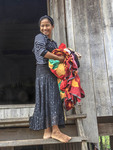 Girl carries laundry into her house in Cham village in Cambodia.
