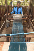 Cambodian woman weaves silk into scarves at a silk farm in Kompong Thom, Cambodia.