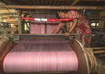 Woman works on mechanical loom making Khmer style cotton scarves on Koh Dach Island off central Phnom Penh, Cambodia.