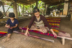 Two women weave  brightly colored straw on a hand loom into mats on Koh Dach Island, a rural island off Phnom Penh, Cambodia.