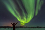 Woman feels joy watching northern lights visible from Churchill River on the tundra outside Churchill, Manitoba, Canada.