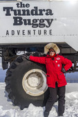 Visitor stands by one of the huge tires used by tundra buggies to travel across the tundra for sighseeing in and around Churchill, Manitoba.