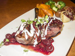 Bacon wrapped bison filet with creamy roqufort cheese sauce and cherries jubilee sauce.