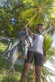 Man holds string of tropical fish he caught with a spear and snorkel gear.