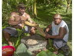 Two local men straighten bamboo bark strips before straining the mildly intoxicating kava liquid through them.
