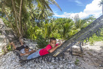 Young local boys lie in a hammock on a beach in Kosrae, Micronesia.