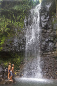 Young native boys play in cascading spray of Sipyen Waterfall, Kosrae,  Micronesia.
