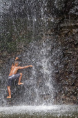 Young native boy plays in cascading spray of Sipyen Waterfall, Kosrae,  Micronesia.