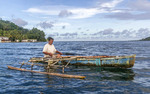 Local man paddles his hand carved outrigger canoe towards the edge of a nearby mangrove swamp to check on his crab traps. Kosrae, Micronesia.