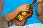 Local boy plays his ukulele. The ukulele is a popular musical instrument on Kosrae, Micronesia, as it is on many Pacific islands.