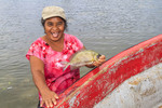 Local woman with rabbitfish, known locally as mulap, caught fishing with a net in shallow waters off the beach in Kosrae, Micronesia.