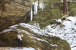 Woman photographs ice formations at Ash Cave, one of several caves with waterfalls in the Hocking Hills State Park system in Ohio, USA.